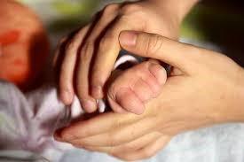赤ちゃんの手を握る母親の手